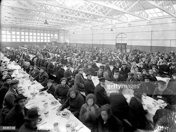 Large group of immigrants sitting down to dinner at the Atlantic Park Hostel in Eastleigh, Hampshire, March 1924. The hostel is mainly used by...