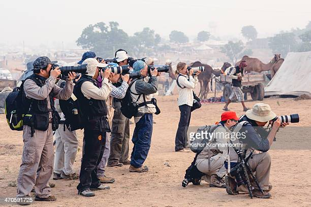 CONTENT] Large group of international photographers pointing all their lenses in the same direction shooting camels at the annual camel fair in India...