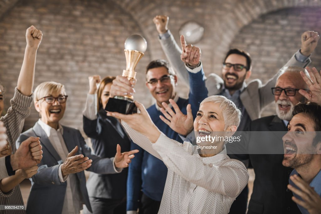 Large group of joyful business colleagues celebrating their success by winning a trophy in the office. : Stock Photo