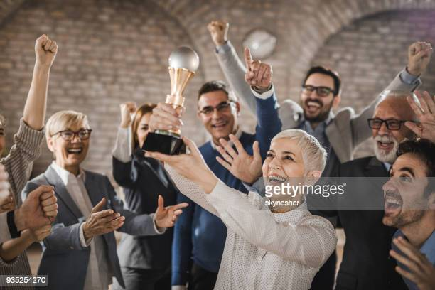 Large group of joyful business colleagues celebrating their success by winning a trophy in the office.