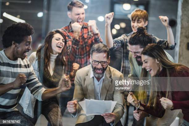 large group of joyful business people celebrating their success in the office. - punching the air stock pictures, royalty-free photos & images
