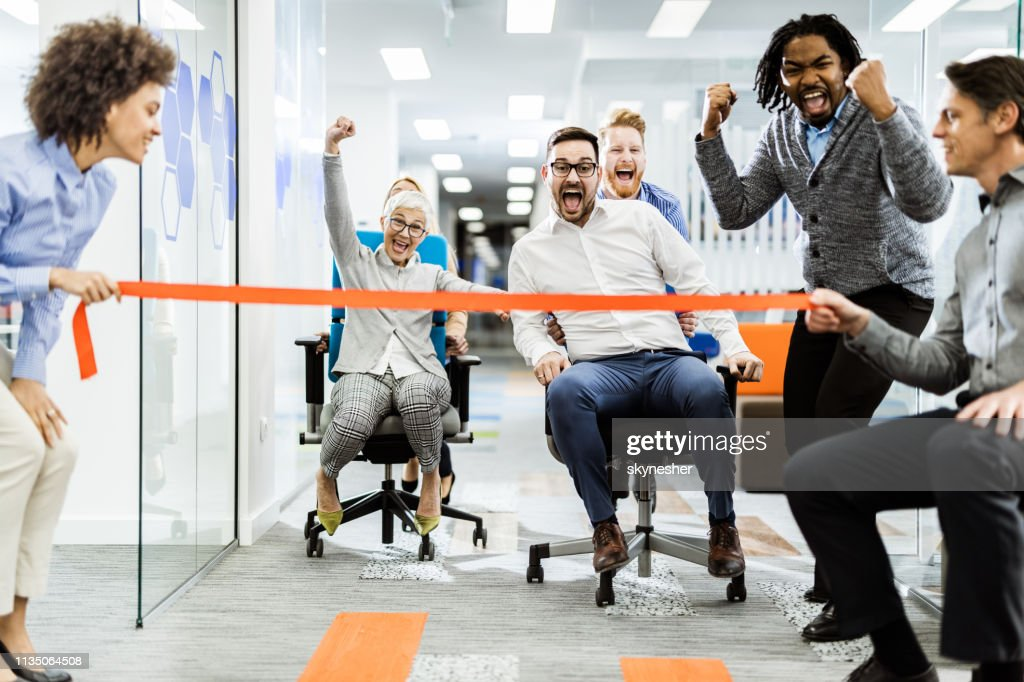 Large group of joyful colleagues having fun during chair race in the office. : Stock Photo