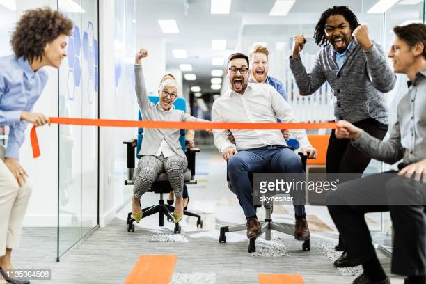 large group of joyful colleagues having fun during chair race in the office. - championship stock pictures, royalty-free photos & images
