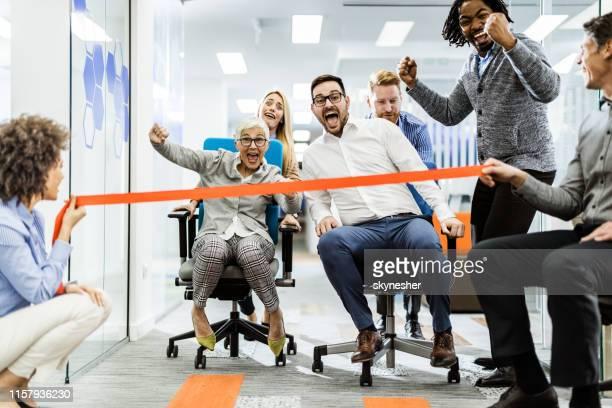 grand groupe de collègues joyeux s'amusant pendant la course de chaise dans le bureau. - chaise de bureau photos et images de collection
