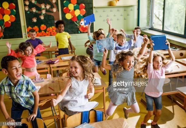 grote groep van vrolijke elementaire studenten springen in de klas. - finale stockfoto's en -beelden