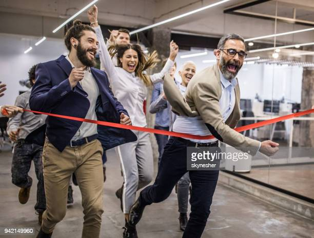 large group of joyful entrepreneurs having fun on a sports race in the office. - finish line stock pictures, royalty-free photos & images