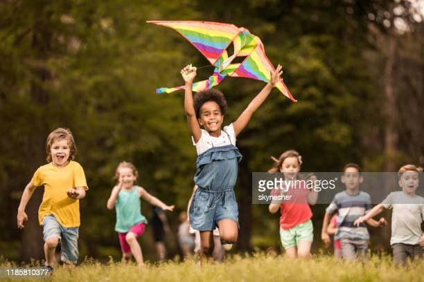 large group of joyful kids running with a kite in springtime. - innocence stock pictures, royalty-free photos & images