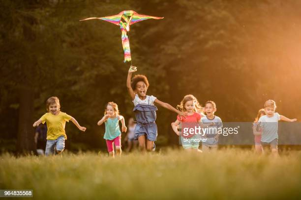 large group of joyful kids running with a kite in springtime. - kite stock pictures, royalty-free photos & images