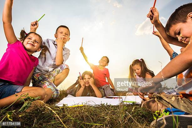 Large group of kids holding their crayons high up outdoors.