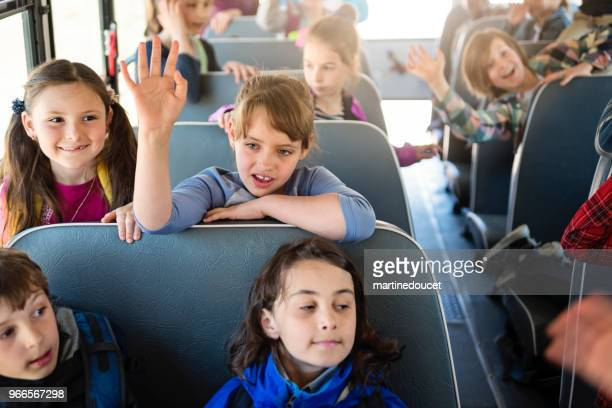 Large group of kids sitting on school bus.