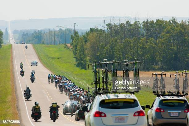 a large group of male bicycle racers ride together in a peloton during a professional road bike race. - cycling event stock pictures, royalty-free photos & images