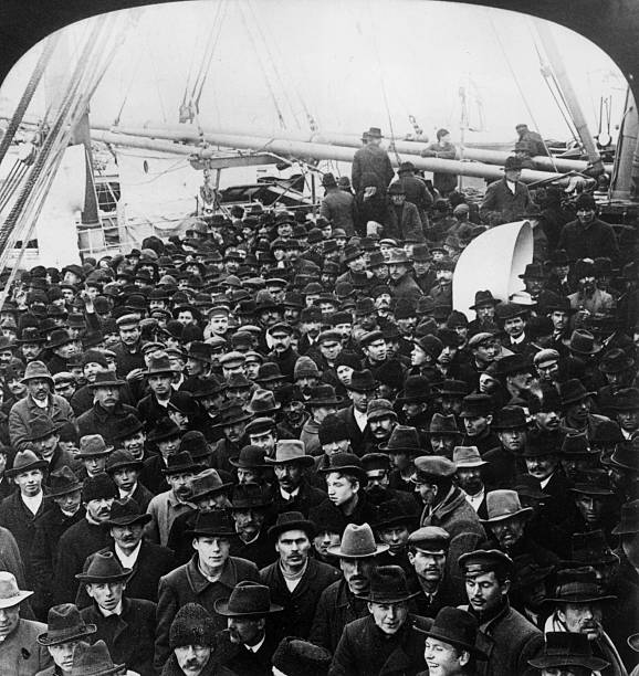 A large group of male immigrants wearing winter coats...