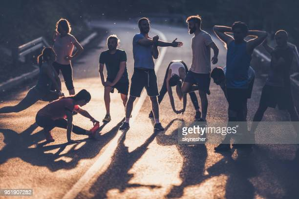large group of marathon runners warming up on a road at sunset. - warming up stock pictures, royalty-free photos & images