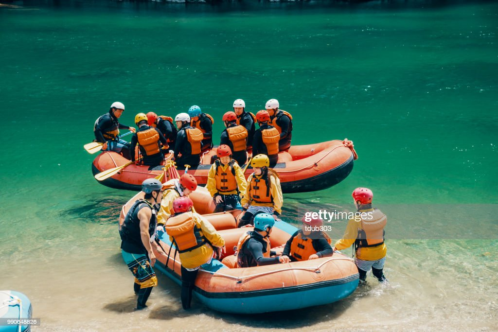 Large group of men and women boarding rafts to go white water river rafting : Stock Photo