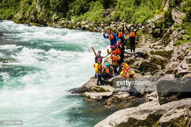 Large group of men and women exploring a riverbank while white water river rafting