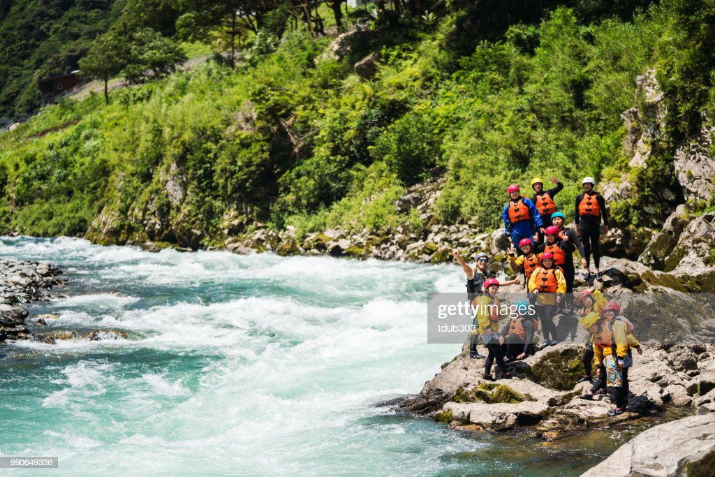 Large group of men and women exploring a riverbank while white water river rafting : Stock Photo