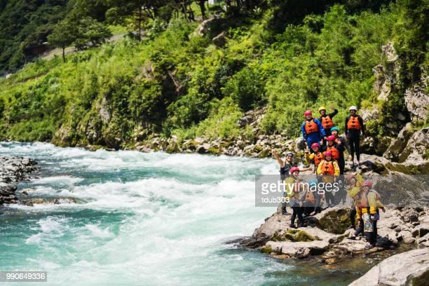 Grote groep van mannen en vrouwen een rivieroever verkennen terwijl white water riverrafting