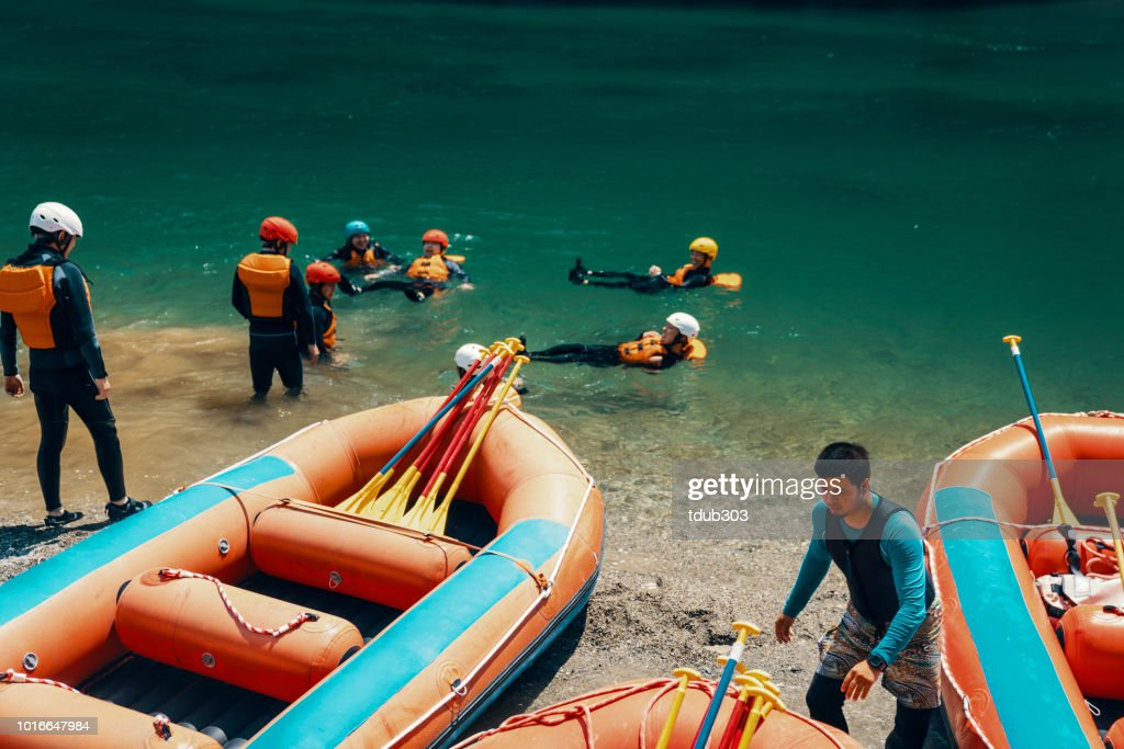 Large group of men and women preparing to go white water river rafting : Stock Photo