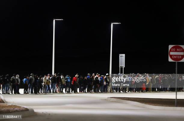 A large group of migrants stand while being detained by border authorities in the early morning hours after crossing to the US side of the USMexico...