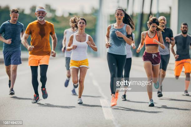 Large group of mix-aged marathon runners on a road.