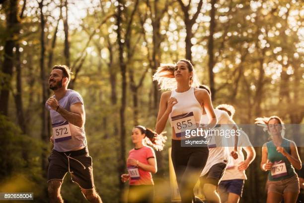 large group of motivated runners running a marathon in nature. - maratona foto e immagini stock