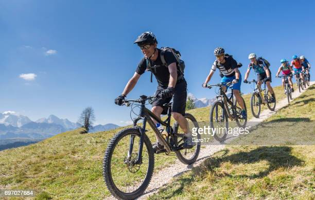 large group of mountainbikers downhill in front of mt. marmolada, italy - cross country cycling stock pictures, royalty-free photos & images