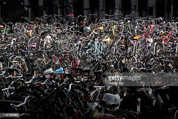a large group of parked bicycles - grote groep dingen stockfoto's en -beelden