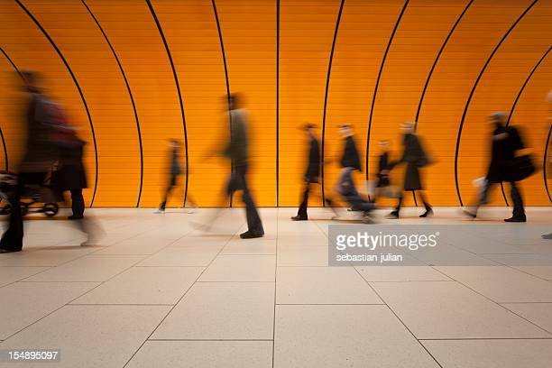 large group of people against modern orange subway tube - railway station stock pictures, royalty-free photos & images