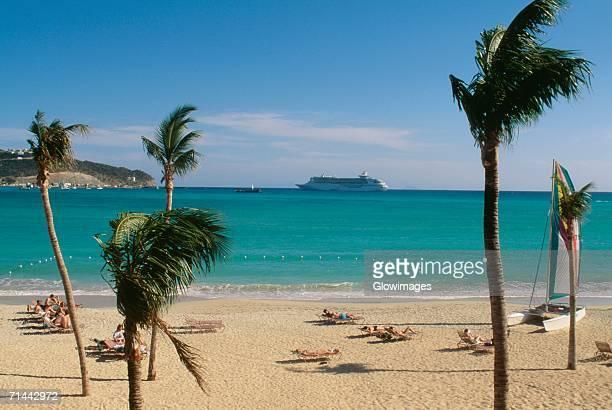 large group of people are sunbathing on deck chairs, st. martin, leewards islands, caribbean - sint maarten stockfoto's en -beelden