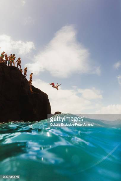 large group of people cliff jumping, waimea bay, oahu, hawaii, usa - waimea bay - fotografias e filmes do acervo