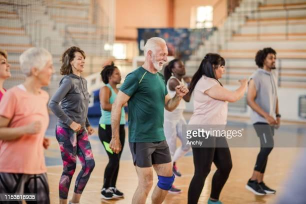 ズンバクラスで踊る大グループの人々 - エクササイズクラス ストックフォトと画像