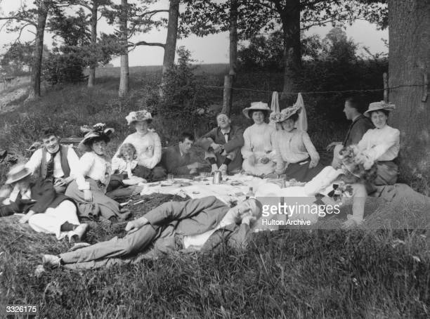Large group of people enjoying a picnic on the grass.