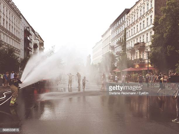 Large Group Of People Enjoying On Street With Firefighter Spraying Water