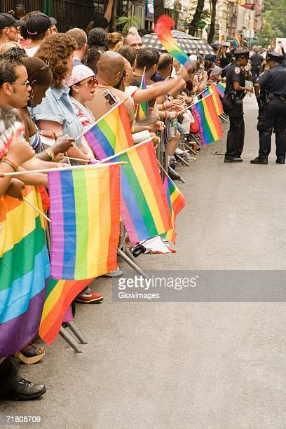 Large group of people holding gay pride flags at a gay parade