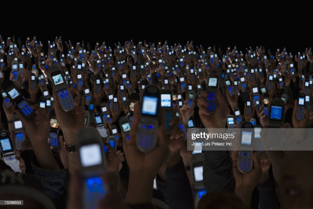 Large group of people holding open cell phones up in air : Stock Photo