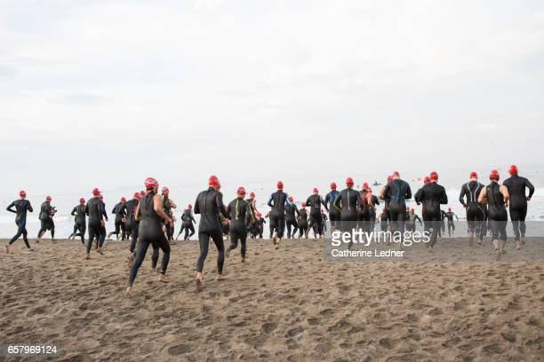 Large group of people in wet suits heading into the ocean