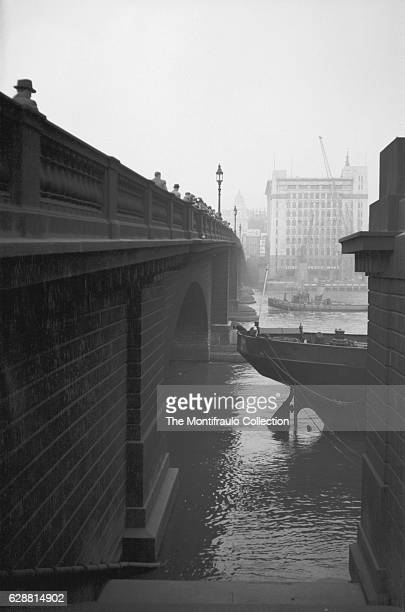 Large group of people looking over London Bridge as a man peers over the side of a steam ship tethered beside the Bridge as a tugboat passes by in...