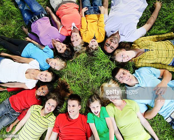 grande gruppo di persone stare sdraiato sull'erba in un cerchio. - grande gruppo di animali foto e immagini stock