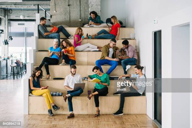 large group of people networking in a loft office - large group of people stock pictures, royalty-free photos & images