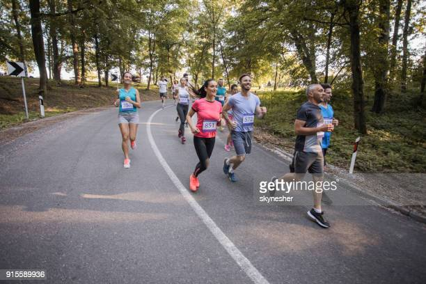 Large group of people running a marathon on asphalt road in nature.