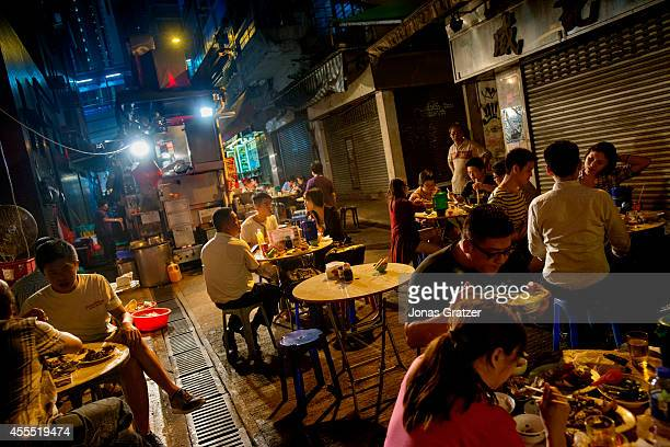 A large group of people sit around small tables in an alleyway to enjoy their street food dinner