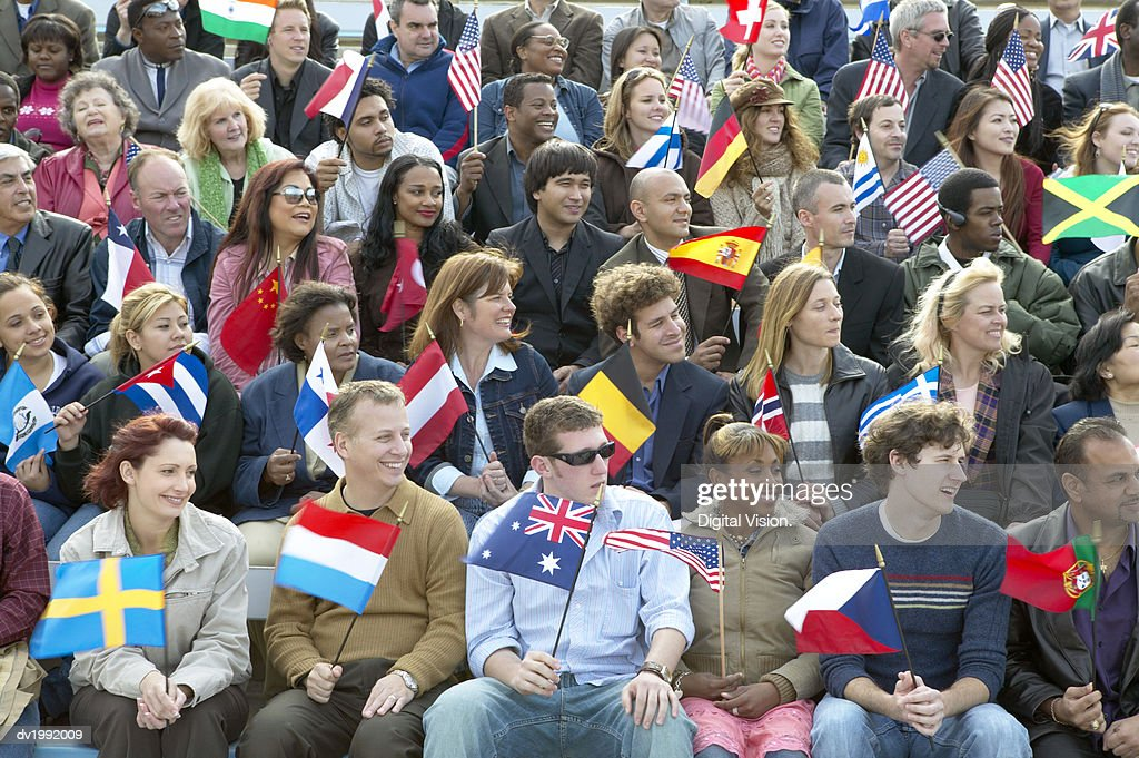 Large Group of People Sitting in Rows and Holding International Flags : Stock Photo