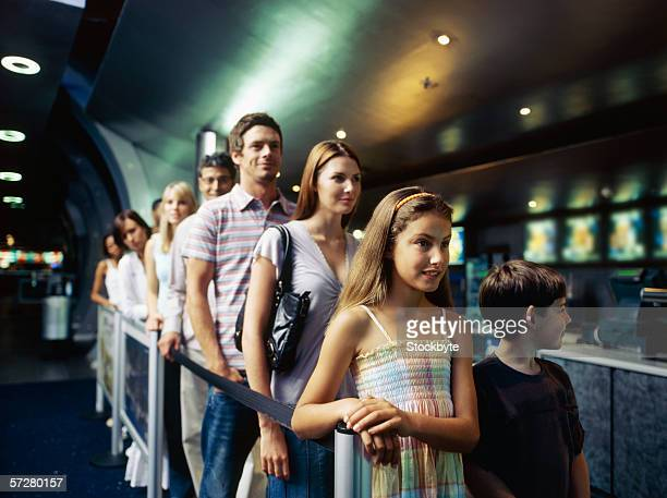 Large group of people standing in a queue inside a cinema