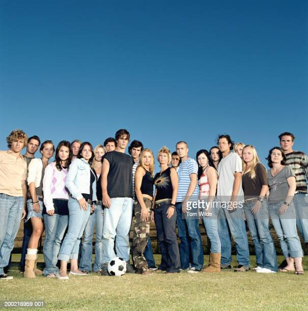 Large group of people standing on grass by football, portrait