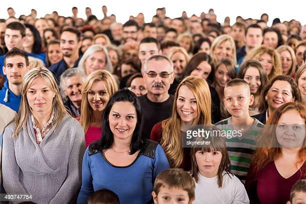 Große Gruppe von Menschen stehen zusammen und Blick in die Kamera.