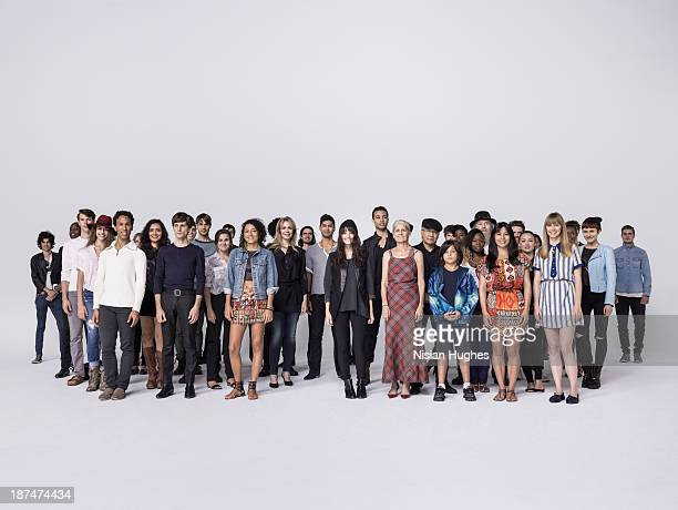 large group of people standing together in studio - large group of people stock pictures, royalty-free photos & images