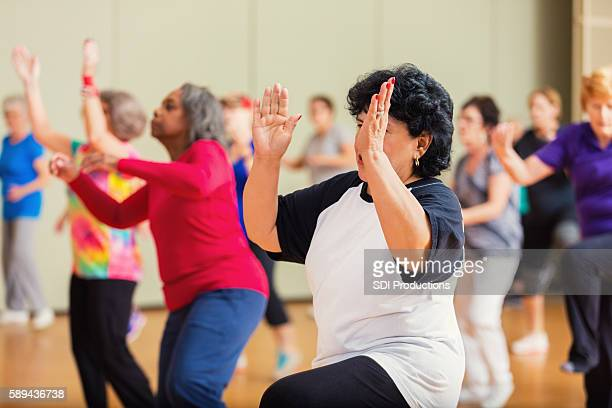 large group of people take dance lessons - community center stock pictures, royalty-free photos & images