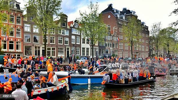 large group of people traveling by boats - king's day netherlands stock pictures, royalty-free photos & images