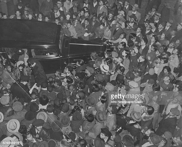 Large group of people waiting to see boxer Joe Louis at night Original Caption Reads 'Any Car Which Stopped In Front Of The Masonic Temple Monday...