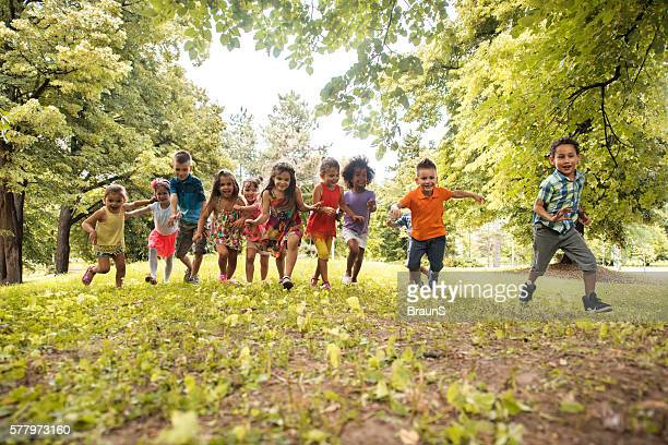 Large group of playful children running in the park.